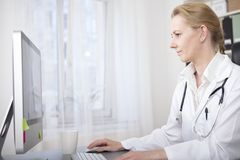 Female Doctor at her Desk Using her Computer. Serious Female Doctor Sitting at her Desk Checking Some Information Through Internet. Captured in Side View Royalty Free Stock Photo