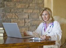 Female Doctor at her desk writing Stock Photos