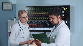 Female doctor and her mixed race collegue discussing EKG data of the athlete. Showed on display in the background. In Scientific Sports Laboratory stock video footage
