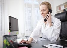 Female Doctor at her Office Dialing a Telephone Royalty Free Stock Photo