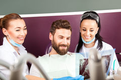 Female doctor and her smiling assistant showing teeth x-ray Royalty Free Stock Image