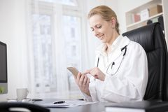 Female Doctor at her Table Browsing on her Phone Royalty Free Stock Photography