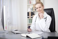 Female Doctor at her Table with Pen and Paper Stock Photo