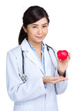Female doctor hodling heart shape squeezing ball Stock Photo