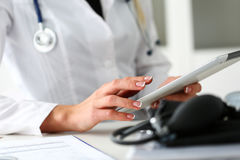 Female doctor hold digital tablet pc. And point in touch screen with finger closeup. Human interaction, professional consultation, therapeutist examine test Stock Image