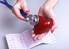 Female doctor hold in hands red toy heart and stethoscope. Cardio therapeutist, arrhythmia concept.  stock image