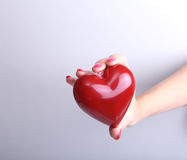Female doctor hold in hands red toy heart and stethoscope. Cardio therapeutist, arrhythmia concept
