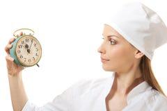 Female doctor holding alarm clock, isolated Royalty Free Stock Photos