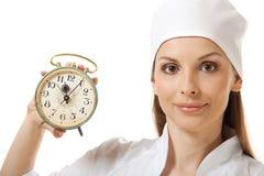 Female doctor holding alarm clock, isolated Stock Photography