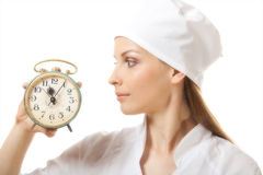 Female doctor holding alarm clock, isolated Royalty Free Stock Photography