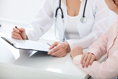 Female doctor holding application form while consulting patient at hospital. Female doctor holding application form while consulting patient stock images
