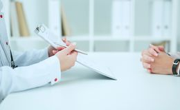 Female doctor holding application form while consulting patient. just hands over the table. Female doctor holding application form while consulting patient Royalty Free Stock Image
