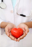 Female doctor holding a beautiful red heart shape Stock Images