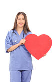 Female doctor holding a big red heart. Isolated on white background Stock Photos