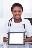 Female doctor holding blank digital tablet at desk Royalty Free Stock Photography