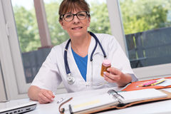 Female doctor holding a bottle of pills Royalty Free Stock Photos