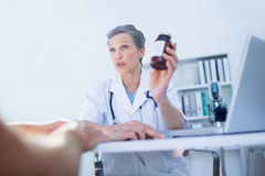 Female doctor holding a box of pills Royalty Free Stock Photo