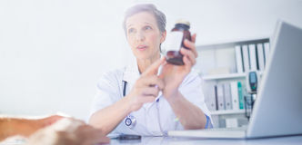 Female doctor holding a box of pills Stock Images
