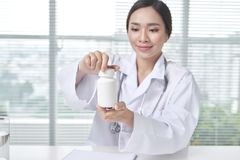Female doctor holding a box of pills in medical office stock photography