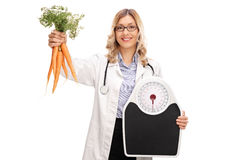 Female doctor holding carrots and a weight scale Stock Photos