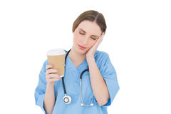 Female doctor holding a coffee mug and lifting her hand to her face with closed eyes Stock Images
