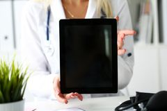 Female doctor holding digital tablet pc. And showing screen to patient. Diagnostics tools and equipment, therapeutist consultation, information search, document Royalty Free Stock Photo