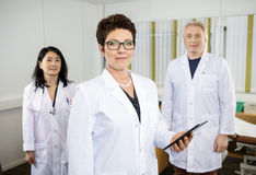 Female Doctor Holding Digital Tablet While Standing With Colleag. Portrait of confident female doctor holding digital tablet while standing with colleagues in stock photography