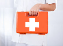 Female Doctor Holding First Aid Box. In hospital Stock Photo