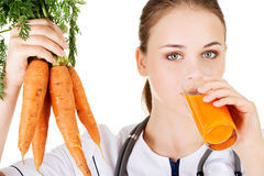 Female doctor holding healthy carrots. Stock Photography