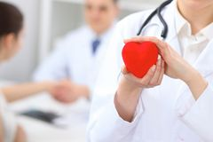 Female doctor holding heart in her hands. Doctor and patient sitting in the background. Cardiology in medicine an. D health care royalty free stock photography