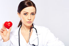 Female doctor holding a heart. Isolated on white background royalty free stock images