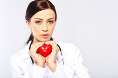 Female doctor holding a heart. Isolated on white background royalty free stock image