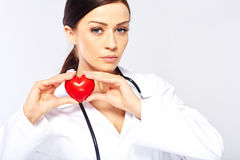Female doctor holding a heart. Isolated on white background stock photography