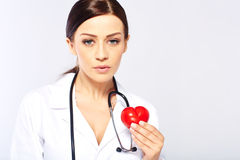 Female doctor holding a heart. Isolated on white background royalty free stock photos
