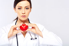 Female doctor holding a heart. Isolated on white background stock image