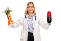 Female doctor holding a huge pill and carrots Royalty Free Stock Photos