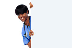 Female doctor holding long blank banner ad. Isolated over white background Royalty Free Stock Image