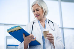 Female doctor holding medical file and coffee cup Royalty Free Stock Photo