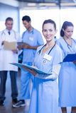 Female doctor holding medical report and smiling at camera. While her colleagues standing in background Royalty Free Stock Photo
