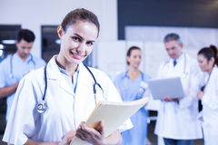 Female doctor holding medical report and smiling at camera Stock Images
