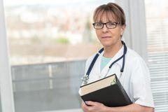 Female doctor holding a medical textbook. Portrait of female doctor standing and holding a medical textbook stock photo
