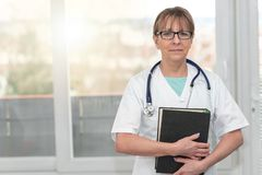 Female doctor holding a medical textbook. Portrait of female doctor standing and holding a medical textbook royalty free stock photography