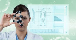 Female doctor holding molecular structure with medical report in background. Digital composite of Female doctor holding molecular structure with medical report Royalty Free Stock Image