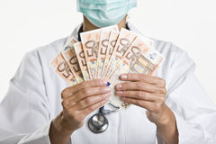 Female doctor holding money Royalty Free Stock Photos