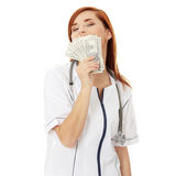 Female doctor holding money Royalty Free Stock Image