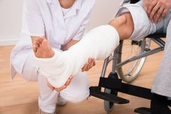 Female doctor holding patient's leg Royalty Free Stock Image