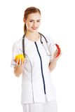 Female doctor holding pepper and chilli Royalty Free Stock Photos