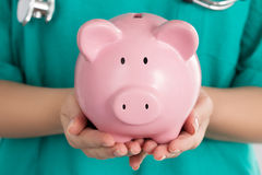 Female Doctor Holding Piggy Bank. Doctor's hands close-up. Medical insurance and health care concept Stock Photography