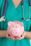 Female Doctor Holding Piggy Bank Stock Images