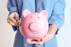 Female doctor holding piggy bank and stethoscope. Close up. Concept of medical insurance Stock Image
